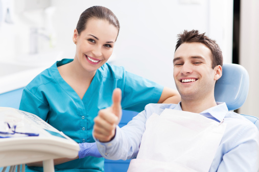 A man giving a thumbs up at a dental office.