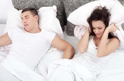 A frustrated woman and her partner snoring in bed.